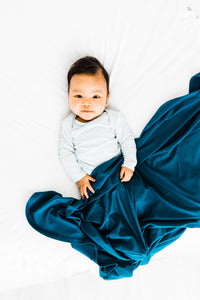 a baby boy covered in our midnight teal stretch swaddle blanket while wearing our kniotted gown in baby blue stripe