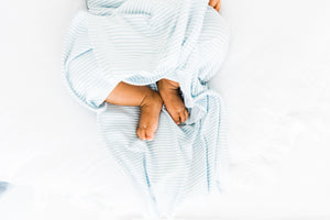 baby feet poking out of our knotted gown in baby blue stripe