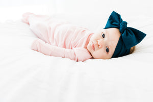 baby girl wearing our knotted baby gown in light pink paired with our headband in midnight teal