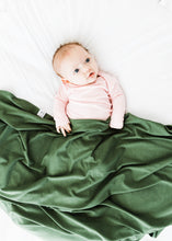 Load image into Gallery viewer, a baby girl wearing our light pink knotted gown while covered with our moss green swaddle blanket