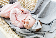 Load image into Gallery viewer, a baby girl laying on our heathered grey swaddle blanket while wearing our knotted gown in light pink and our headband in heathered grey