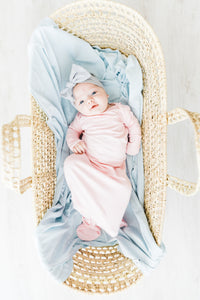 a baby girl laying in a bassinet with our baby blue stripe swaddle blanket. she's also wearing our knotted gown in light pink and headband in heathered grey