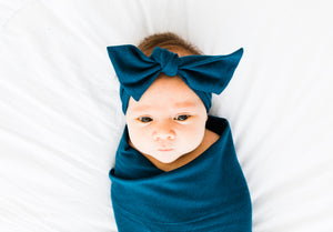 baby girl wrapped in our bamboo stretch swaddle blanket and wearing our headband in midnight teal