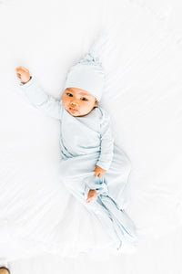a baby boy wearing our baby blue stripe top knot hat and knotted gown