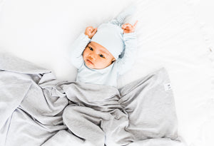 a baby boy wearing our baby blue stripe knotted gown and top knot hat while covered in our swaddle blanket in heathered grey