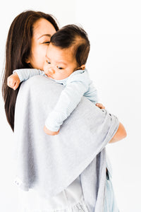 a mom holding her baby boy with our heathered grey swaddle blanket drapped over her shoulder