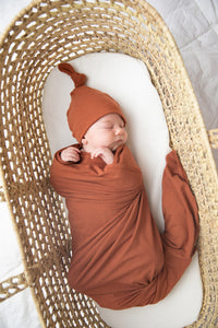 Baby wrapped in our Rust coloured swaddle and wearing matching top knot hat in rust