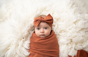 Baby wearing our top knot headband in Rust