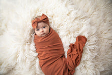 Load image into Gallery viewer, baby girl wrapped in our rust coloured swaddle blanket with matching headband