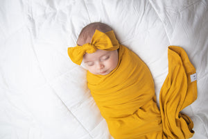 Baby wearing our mustard headband wrapped in our mustard swaddle