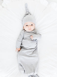 a baby boy wearing our heathered grey top knot hat and heathered grey knotted gown
