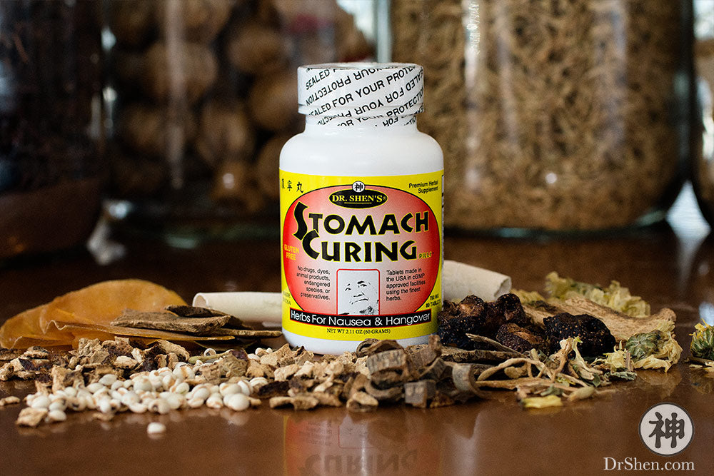Bottle of Stomach Curing Pills surrounded by raw Chinese herbs