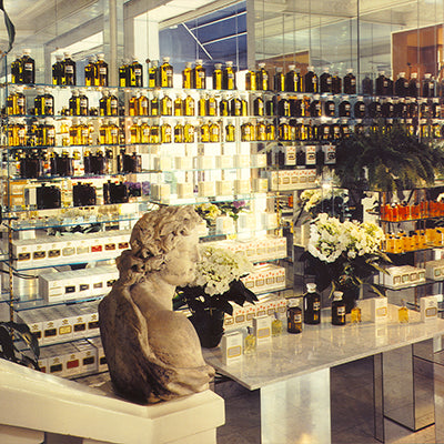 Shelves of Creed fragrances behind a counter with a bust.