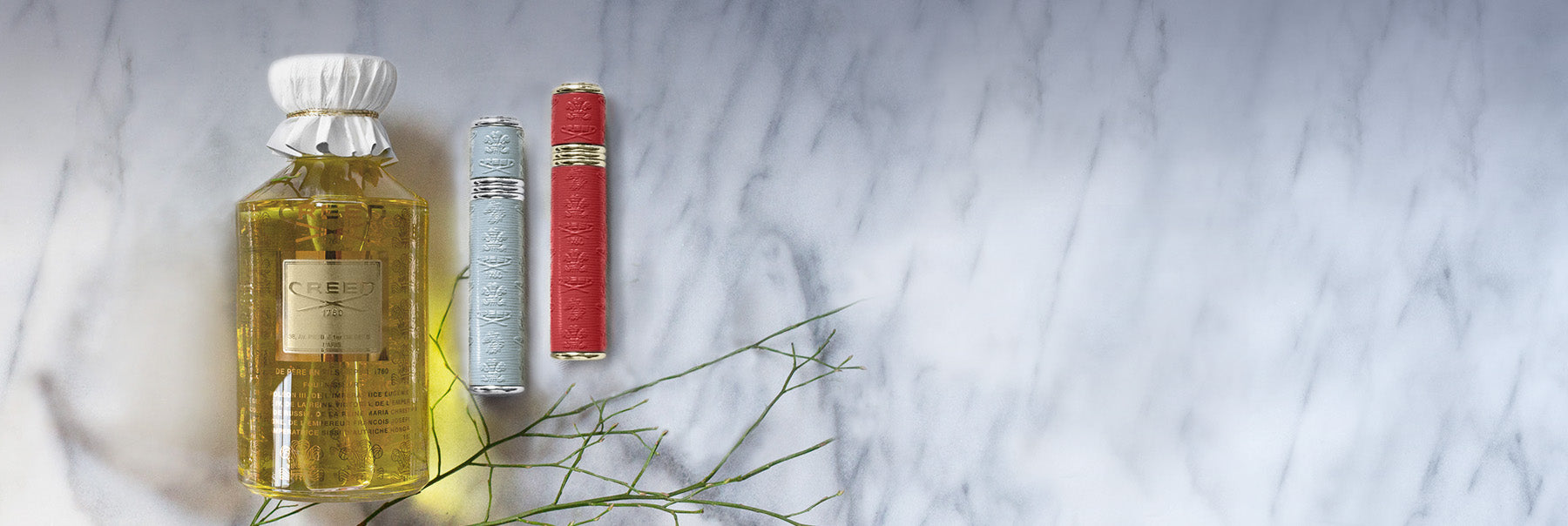 A Flacon and a red atomizer and grey atomizer against a marble backdrop
