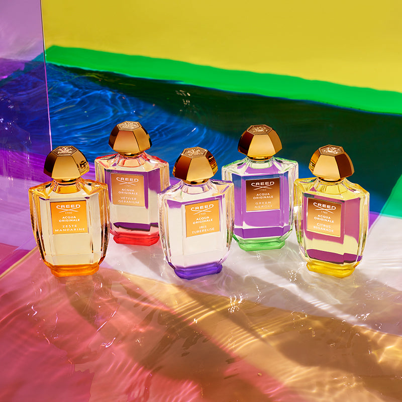 Zeste Mandarin, Vetiver Geranium, Iris Tubereuse, Green Neroli, and Citrus Bigarrade fragrance bottles against a colorful aquatic-like backdrop