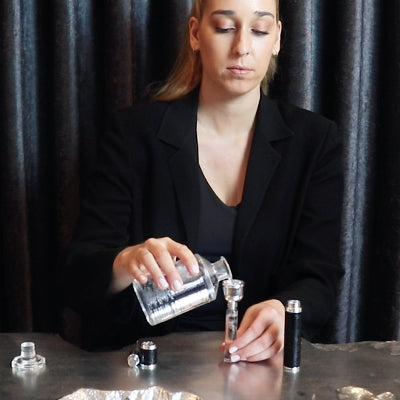 Woman filling a leather atomizer with a Creed flacon fragrance