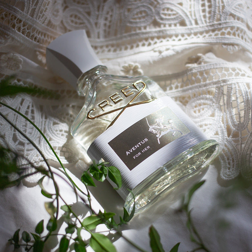 A bottle of Aventus for her against white lace fabric and a spring of green leaves