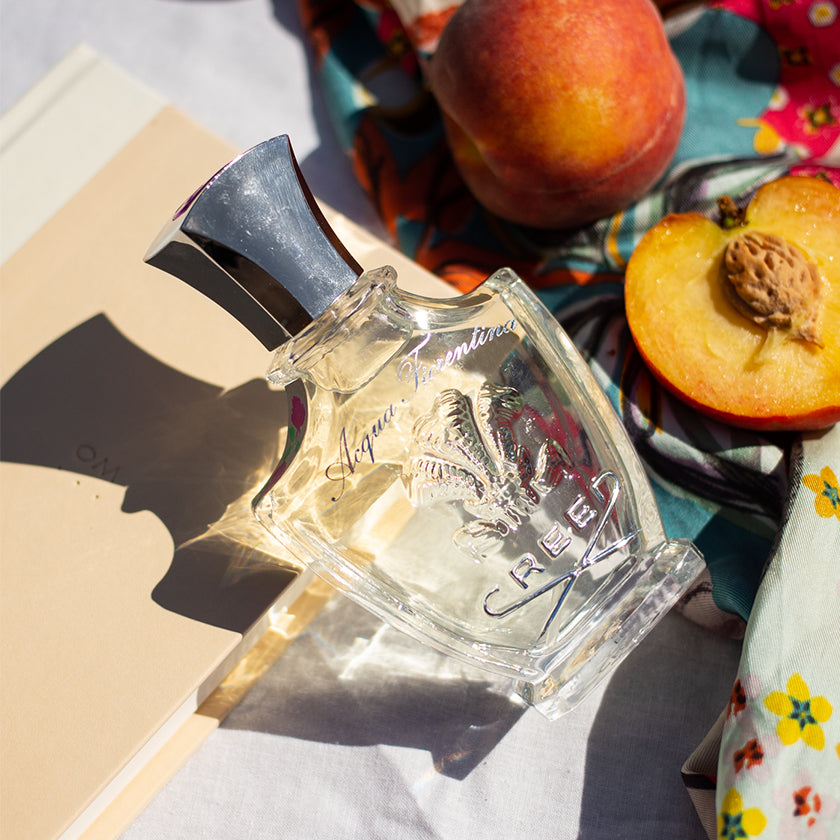 A  bottle of Acqua Fiorentina in the sunlight next to peaches