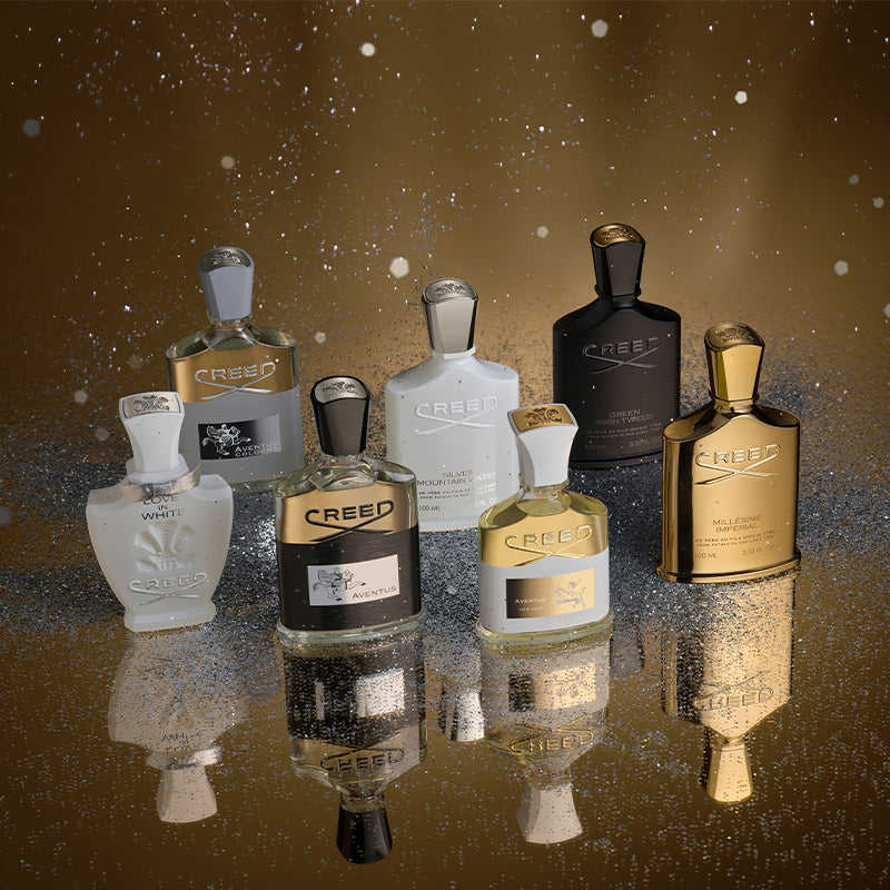 From Left to Right, a bottle of Love In White, Aventus Cologne, Aventus, Silver Mountain Water, Aventus For Her, Green Irish Tweed, and Millésime Impérial against a glittery background with Holiday Gift Guide written in script across the top