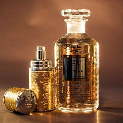 Gold Atomizer with Silver Trim next to a Flacon of Aventus, bathed in a golden light