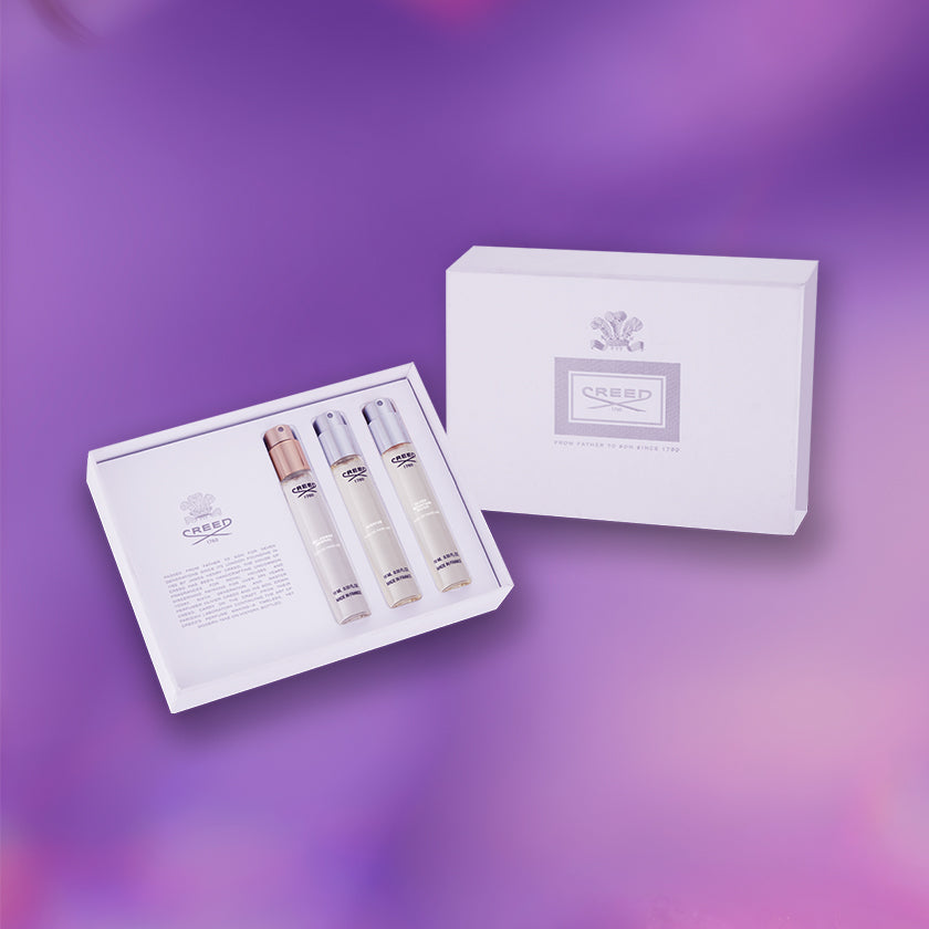 Creed's Mother's Day Les Essentiel's Coffret featuring three 10ml vials of Silver Mountain Water, Aventus For Her and Love in White against purple iridescent background.