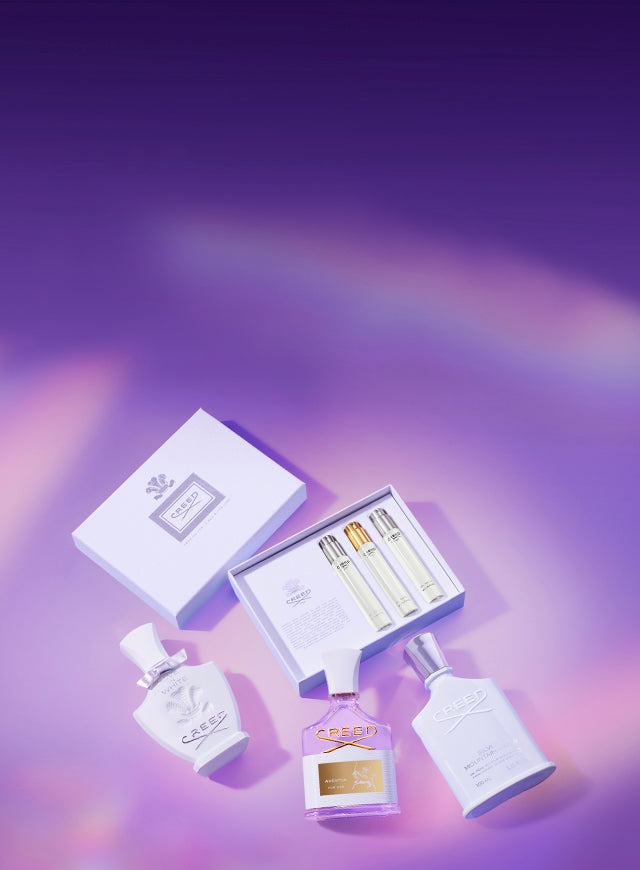 Creed's Mother's Day Les Essentiels Coffret including three 10ml vials of Love In White, Aventus For Her and Silver Mountain Water along with three 75ml bottles of the same fragrances on a purple iridescent background.