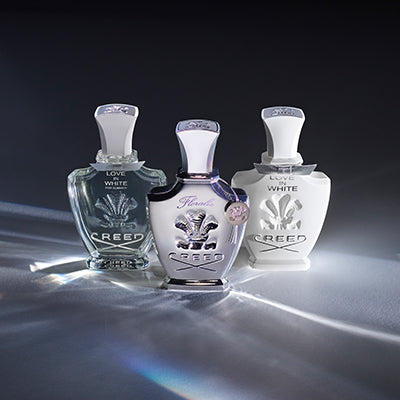 75 ml bottles of Love In White For Summer, Floralie, and Love In White against a refractive backdrop