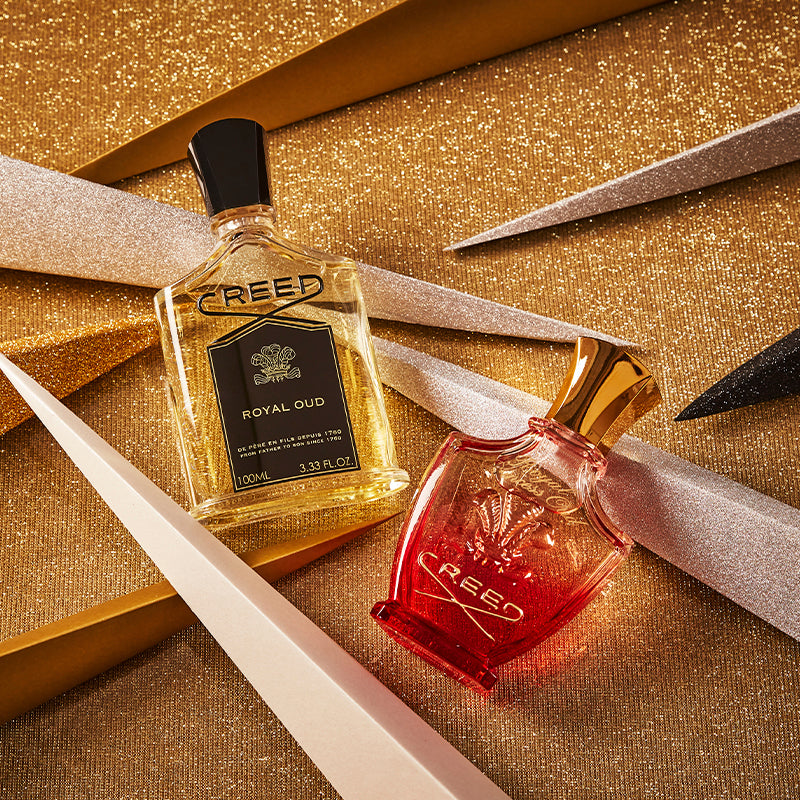 100ml bottle of Royal Oud and 75ml bottle of Royal Princess Oud fragrances against a glittering backdrop