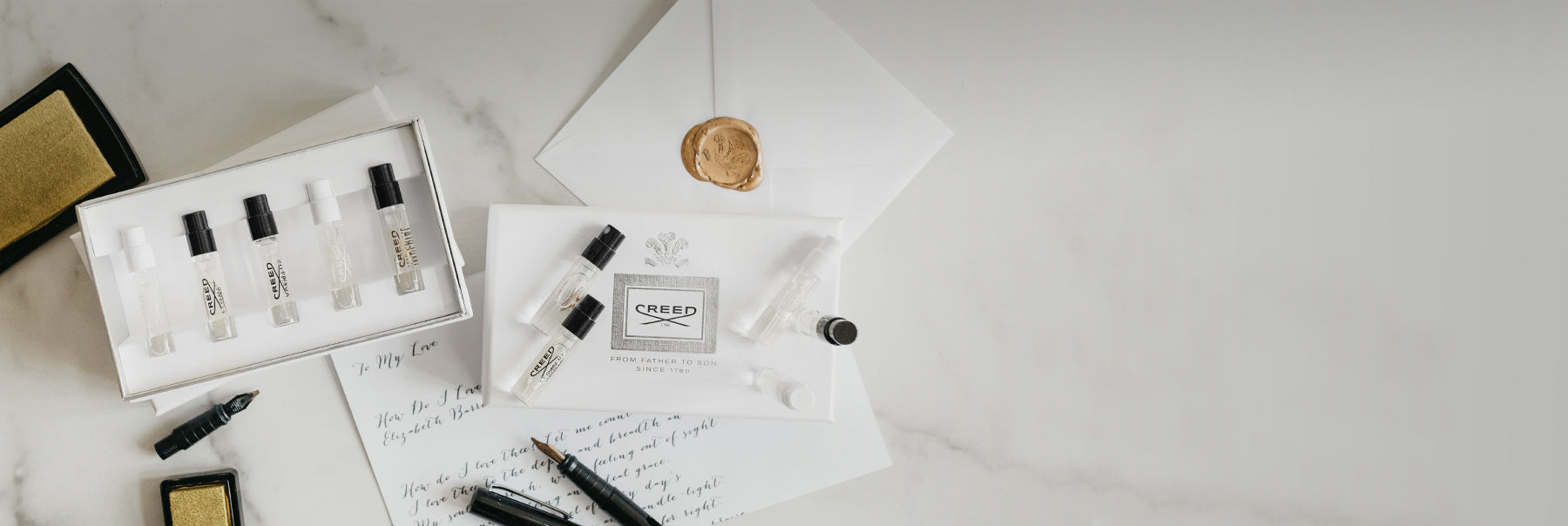 Open box of 5 sample fragrance vials and a closed box of sample vials on a stationary set with pens and envelopes