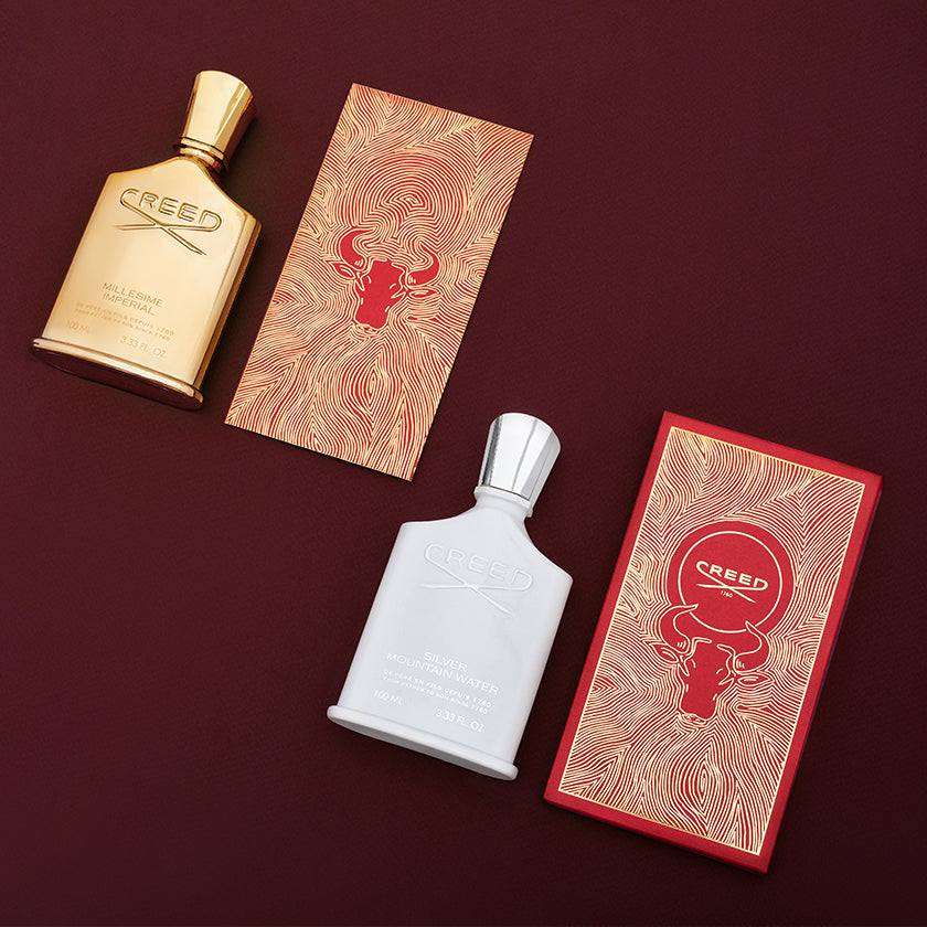 Gold fragrance bottle and white fragrance bottle next two red envelopes with gold ox designs