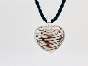 Murano clear glass heart pendant with white center and burgundy swirls on a black coiled necklace