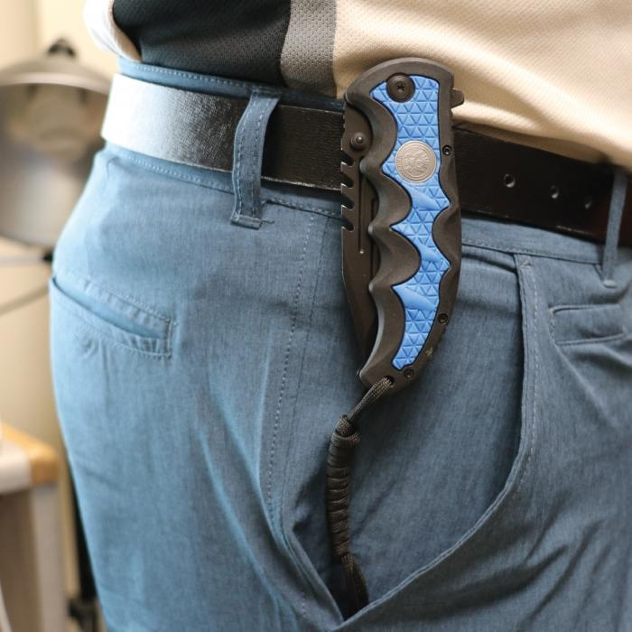 Image shows navy blue knife with belt clip how it appears when worn.