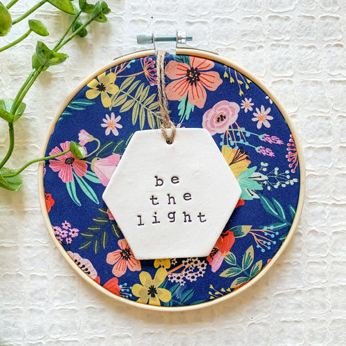 6 Inch Hoop with Navy Floral Fabric and Hand Stamped Ivory Clay Hexagon 'Be the Light' Ornament