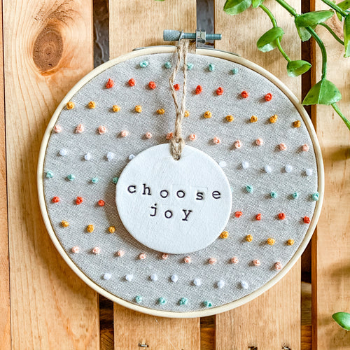 6 Inch Hoop with Natural Tan Linen Fabric, Hand Stitched French Knots, and Hand Stamped Ivory Clay Circle 'Choose Joy' Ornament