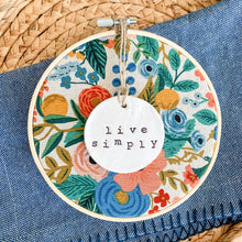 Load image into Gallery viewer, 6 Inch Hoop with Rifle Paper Co. Garden Party Canvas Fabric and Hand Stamped Ivory Clay Circle 'Live Simply' Ornament