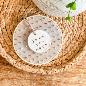 5 Inch Hoop with Natural Tan Linen Fabric, Hand Stitched French Knots, and Hand Stamped Ivory Clay Circle 'Love You More' Ornament