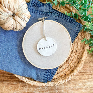 6 Inch Hoop with Natural Tan Linen Fabric and Hand Stamped Ivory Clay Circle 'Blessed' Ornament