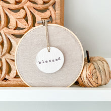 Load image into Gallery viewer, 6 Inch Hoop with Natural Tan Linen Fabric and Hand Stamped Ivory Clay Circle 'Blessed' Ornament