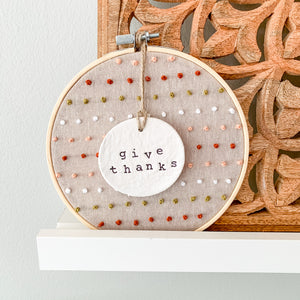 6 Inch Hoop with Hand Stitched French Knots on Natural Linen Fabric and Hand Stamped Ivory Clay Circle 'Give Thanks' Ornament