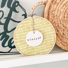 Load image into Gallery viewer, 6 Inch Hoop with Green Dash Fabric and Hand Stamped Ivory Clay Circle 'Blessed' Ornament