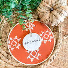 Load image into Gallery viewer, 6 Inch Hoop with Spiced Red Quilt Fabric and Hand Stamped Ivory Clay Circle 'Grateful' Ornament
