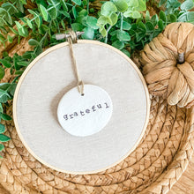 Load image into Gallery viewer, 6 Inch Hoop with Natural Tan Linen Fabric and Hand Stamped Ivory Clay Circle 'Grateful' Ornament