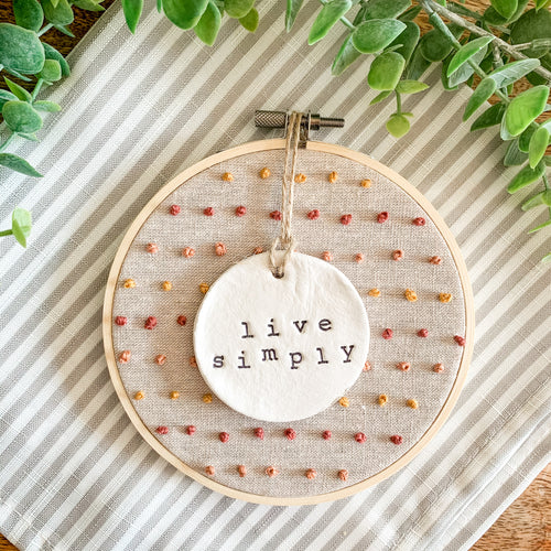 5 Inch Hoop with Natural Tan Linen Fabric, Hand Stitched French Knots, and Hand Stamped Ivory Clay Circle 'Live Simply' Ornament