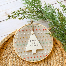 Load image into Gallery viewer, 6 Inch Hoop with Hand Stitched French Knots on Natural Linen Fabric and Hand Stamped Ivory Clay Tree 'Let it Snow' Ornament