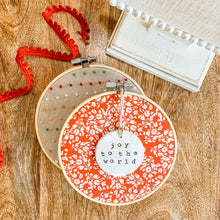 Load image into Gallery viewer, 6 Inch Hoop with Cardinal Red Frosty Floral Fabric and Hand Stamped Ivory Clay Circle 'Joy to the World' Ornament