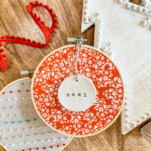 Load image into Gallery viewer, 6 Inch Hoop with Cardinal Red Frosty Floral Fabric and Hand Stamped Ivory Clay Circle 'Noel' Ornament