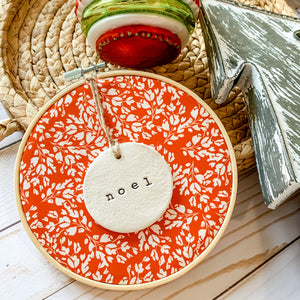 6 Inch Hoop with Cardinal Red Frosty Floral Fabric and Hand Stamped Ivory Clay Circle 'Noel' Ornament