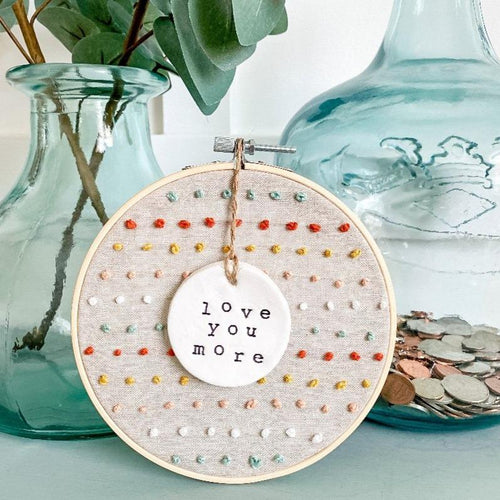 6 Inch Hoop with Natural Tan Linen Fabric, Hand Stitched French Knots, and Hand Stamped Ivory Clay Circle 'Love You More' Ornament