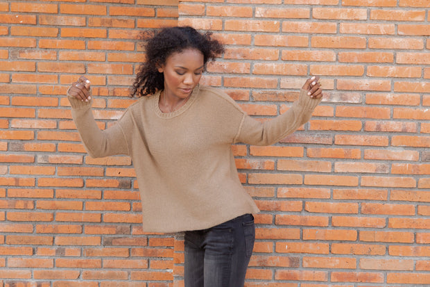Woman wearing camel colored lightweight sweater with ribbed neckline and cuffed sleeves