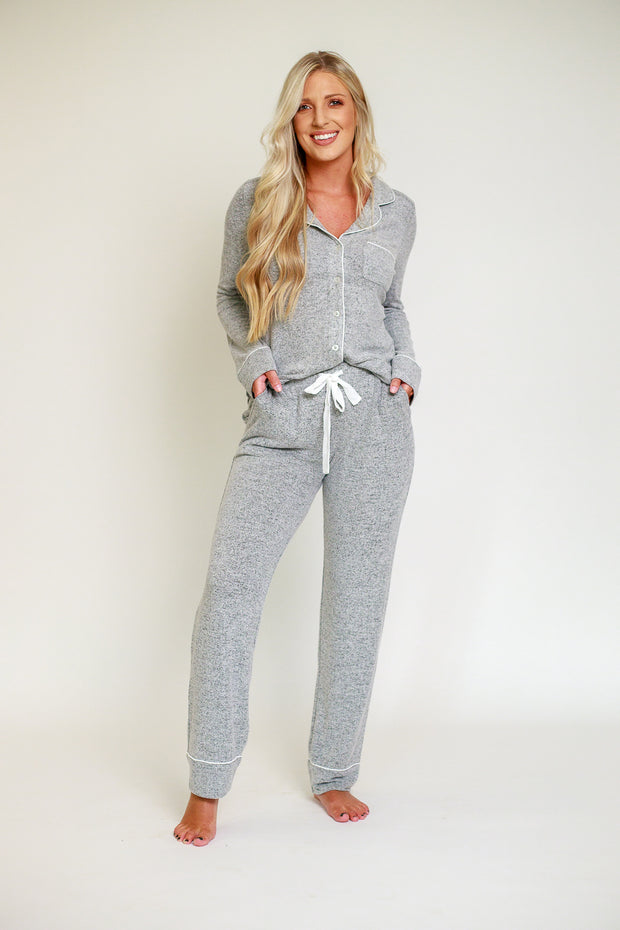 Woman wearing grey pajama set in comfortable fabric with contrast piping